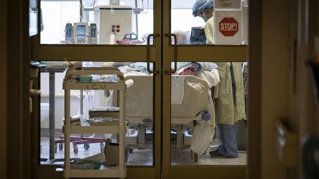 Un lit d'hôpital derrière des portes vitrées.