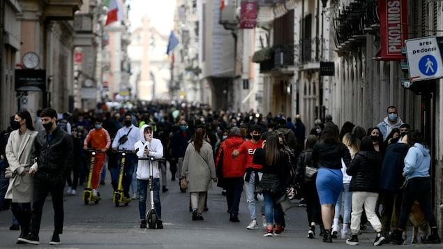 Une foule très importante marche sur le pavé.