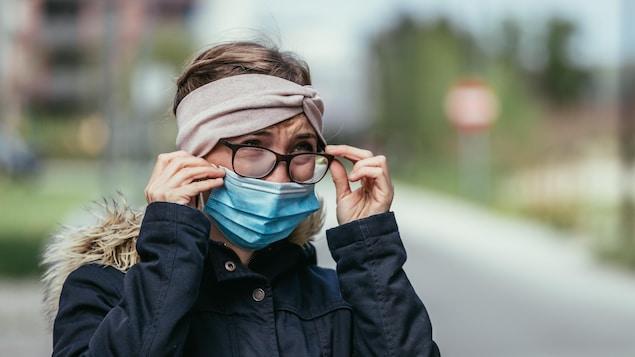 On voit une femme qui porte un masque protecteur et qui est en train d'enlever ses lunettes pleines de buée.