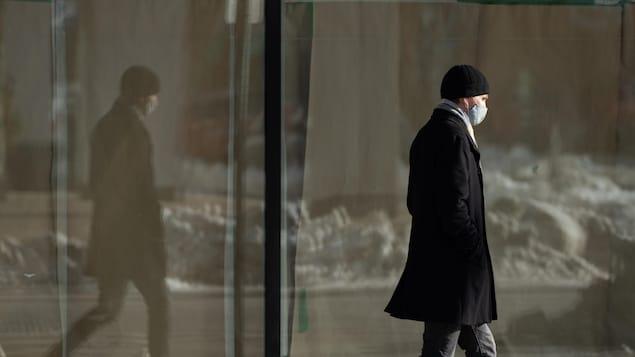 Un homme portant un masque marche sur un trottoir enneigé.