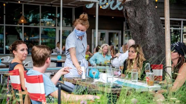 Une serveuse portant un masque sert des clients qui n'en portent pas.