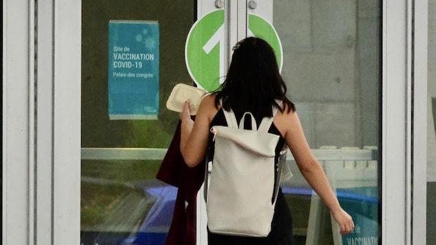 Une dame se dirige vers un centre de vaccination.