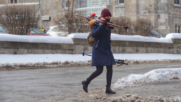 Une femme transporte des skis alpins en marchant dans la rue.