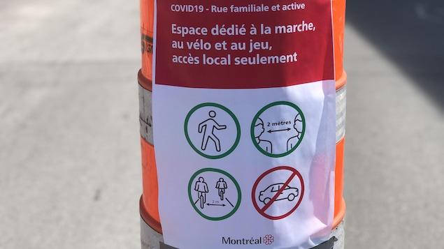Une affiche avec notamment des indications de distanciation sociale sur un cône de signalisation.