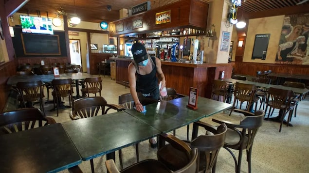 A server cleans tables at an empty pub, Wednesday, July 22, 2020, in Montreal.