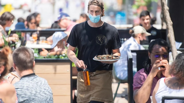 A server brings an order to a customer at a restaurant in Montreal on June 6, as the COVID-19 pandemic continues in Canada and around the world.