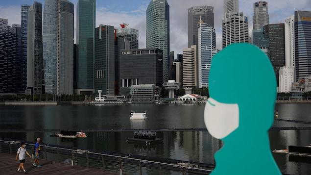 Une statue portant un masque devant une vue de la marina de Singapour.
