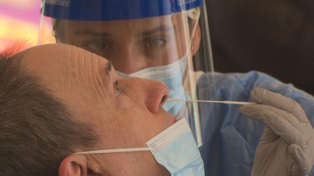 Une infirmière effectue un test de dépistage de la COVID-19 sur un patient.