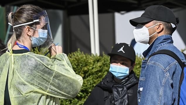 Une travailleuse de la santé portant masque et visière pose des questions à des clients dans un centre de dépistage.