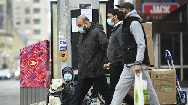 Trois hommes portant un masque passent dans la rue à côté d'un mendiant assis au sol, qui porte lui aussi un masque.