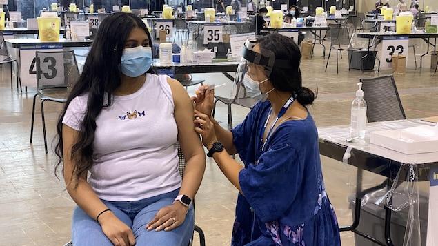 Une Torontoise se fait injecter le vaccin dans l'épaule dans un centre d'immunisation de masse.