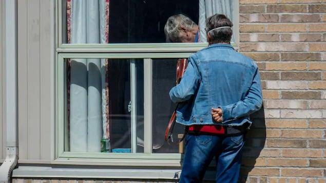 Un homme parle à un autre homme à la fenêtre.
