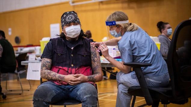 Tinuturukan ng health-care worker ang isang lalaki na naka-mask sa loob ng basketball court.