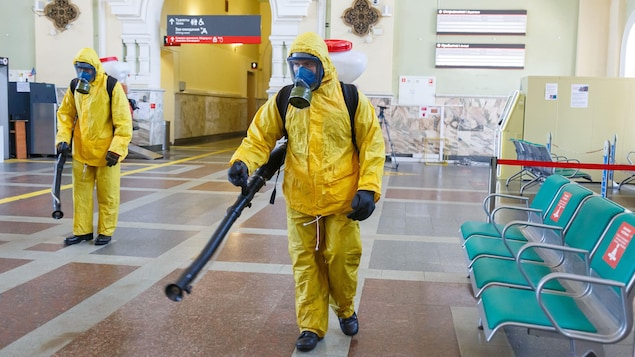 Deux hommes en habit de protection allant de la tête aux pieds désinfectent une station.