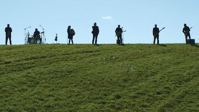 7 musiciens et musiciennes sont debouts sur une colline de verdure et jouent de la musique.
