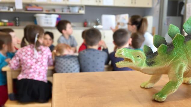 Des enfants écoutent une éducatrice leur faire la lecture.