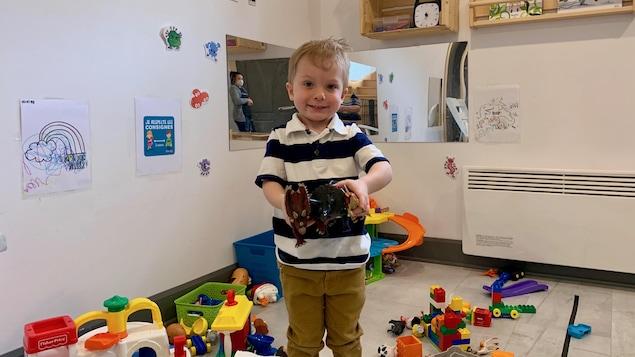 Un garçon tient des dinosaures en plastique dans une garderie.