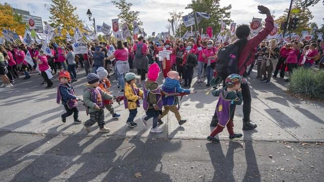 Des enfants d'âge préscolaire passent avec leur éducatrice devant la manifestation.