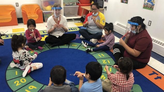 Des enfants et leurs éducatrices sont assis en cercle sur un tapis ludique et jouent de la flûte.