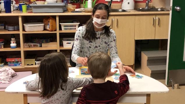 Une éducatrice porte un masque transparent en jouant avec deux enfants.