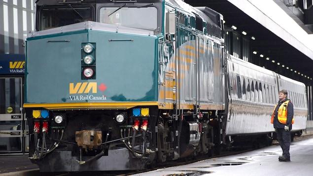 Photo d'un employé vêtu d'un dossard orange à côté d'une locomotive verte tirant deux wagons dans une gare.