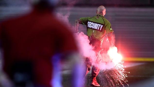 Un agent de sécurité court sur le terrain avec un object en feu dans sa main.