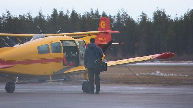 Une personne debout sur le tarmac devant un avion dont la porte d'accès au cockpit est ouverte.