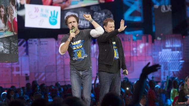 On voit les deux cofondateurs d'UNIS sur la scène, qui parlent au micro et saluent la foule.