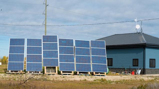 Des panneaux solaires derrière un édifice bleu
