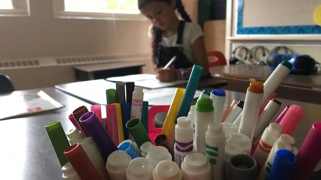 Un pot rempli de crayons de couleurs et une fillette qui dessine en arrière-plan
