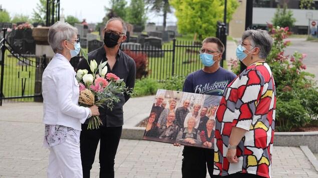 Quatre membres de la famille tiennent des objets qu'ils laisseront sur la tombe de leur mère décédée, il y a un an.