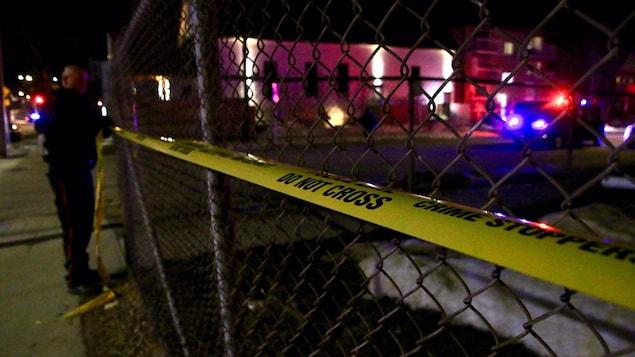 Un policier pose un ruban jaune sur une clôture pour interdire l'accès à la zone ainsi délimité.