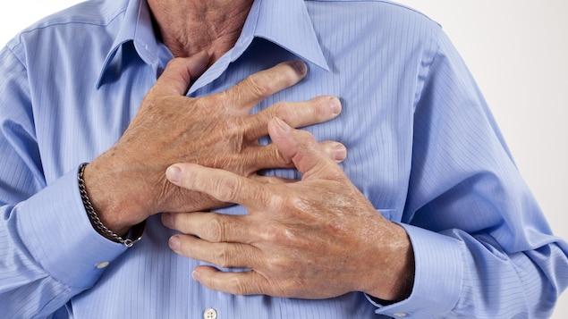 Un homme se serre la poitrine en raison de douleurs.