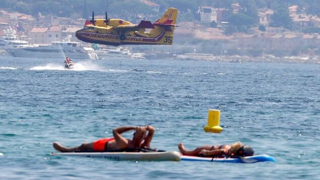 Deux vacanciers flottent sur des planches avec, en arrière-plan, un canadair survolant l'eau.