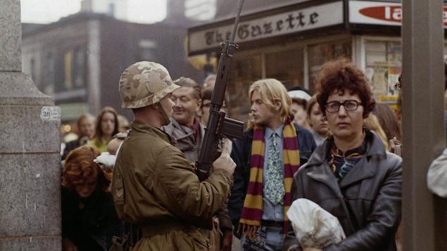 Un soldat monte la garde à une intersection du centre-ville de Montréal lors de l'entrée en vigueur de la Loi sur les mesures de guerre, en octobre 1970