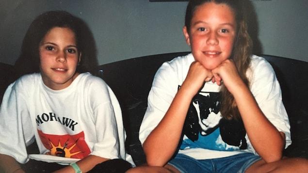 Deux jeunes filles assises sur un lit. La photo date des années 1990.
