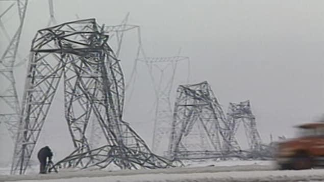 Un caméraman filme une rangée de pylônes électriques en acier pliés en deux sous le poids de la glace.