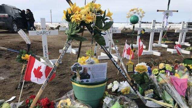 Bâtons de hockey, fleurs et drapeaux devant les croix.