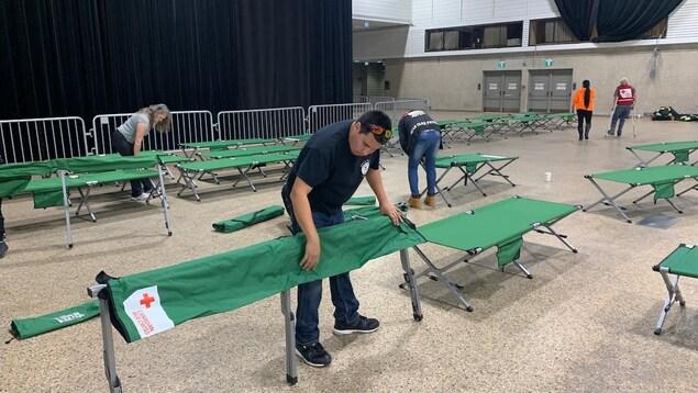 Des bénévoles installent des lits de camp dans le Centre des congrès RBC de Winnipeg.