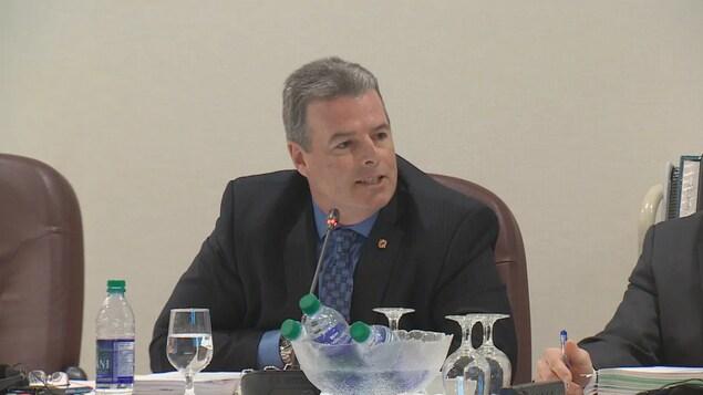 Keith Cronkhite, assis à une table durant une assemblée publique.