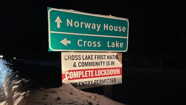 Une pancarte routière dans le noir indique les communautés de Norway House et de Cross Lake. Sous ces indications, une autre pancarte précise que la Première Nation de Cross Lake est en fermeture d'urgence.
