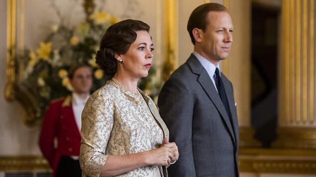 Une femme porte une tenue imprimée et un collier de perles, et l'homme porte une veste grise.