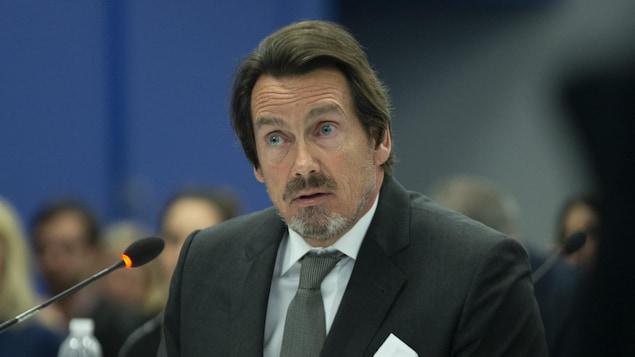 Pierre Karl Péladeau assis, devant un micro.