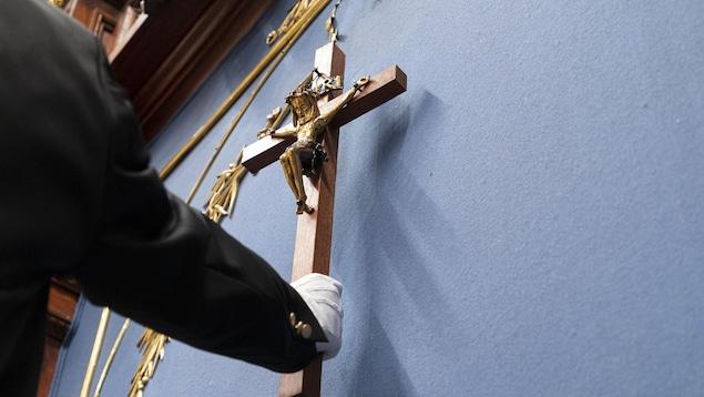 Un employé de l'Assemblée nationale retire le crucifix du Salon bleu. Il porte des gants blancs.