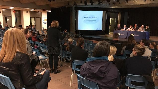 Des parents réunis dans un agora pour une rencontre avec une femme qui pose des questions à un panel.