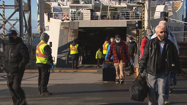 Des usagers avec leurs bagages sortent du bateau.