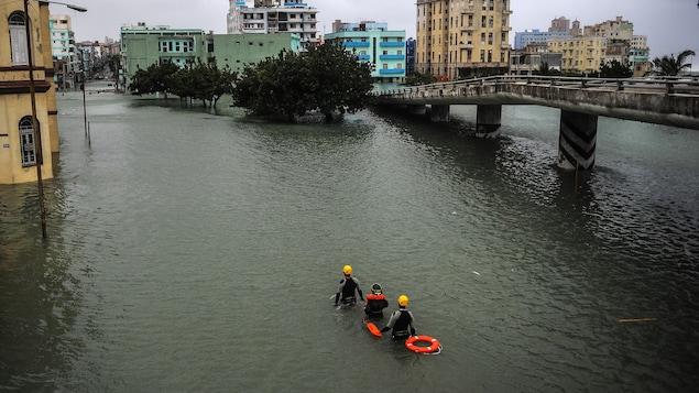 Des secouristes sont photographiés de haut en train de marcher dans la capitale cubaine inondée.