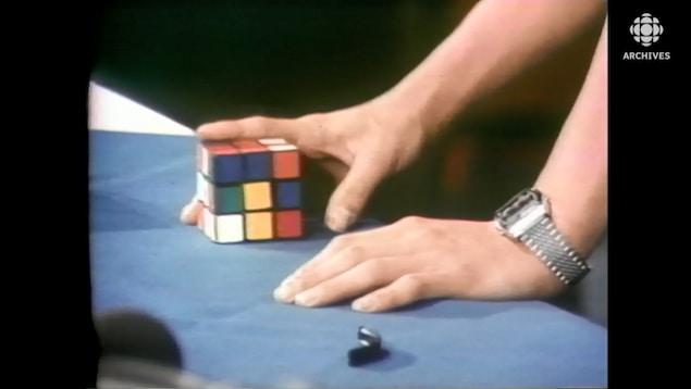 Une main étudie un cube Rubik.