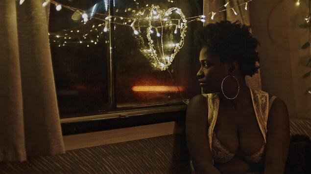 Une femme regarde par la fenêtre de sa caravane.