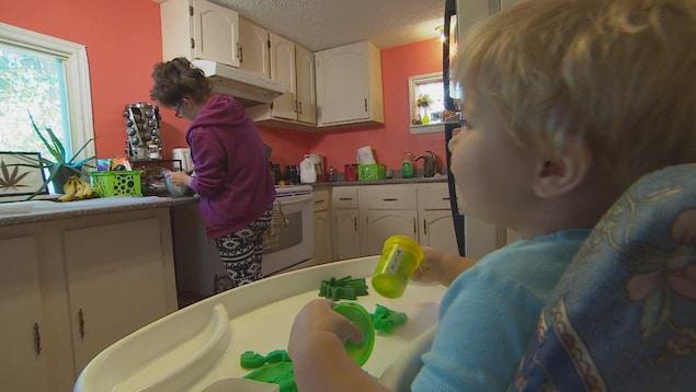 Une femme cuisine avec du cannabis chez elle avec son enfant qui l'observe, dans sa chaise haute.